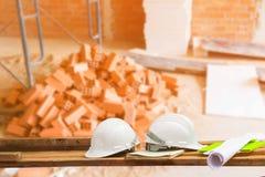Пластмасса и светокопия шлема безопасности на древесине с предпосылкой рабочего места строительной площадки конструкции нерезкост стоковые изображения