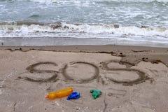 Проблема окружающей среды Концепция экологичности Пластмасса на пляже с сочинительством sos Разлитый отброс на пляже стоковая фотография