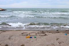 Проблема окружающей среды Концепция экологичности Пластмасса на пляже с сочинительством sos Разлитый отброс на пляже стоковое фото rf
