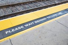 Платформа поезда со знаком пожалуйста ждет за желтой линией и желтой маркированной предупреждающей областью стоковые фотографии rf