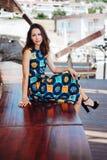 Платье брюнет сидя на стенде Стоковые Фото