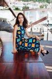 Платье брюнет сидя на стенде Стоковая Фотография