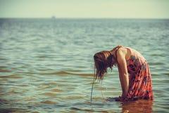 Платье девушки малыша нося играя в воде Стоковые Изображения RF