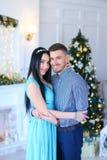 Платье кавказской женщины нося стоя с супругом около камина и рождественской елки стоковое изображение