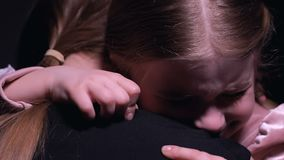 Плача маленькая девочка обнимая мать и смотреть камеру, страдая от задирать акции видеоматериалы