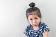 Плача милая маленькая азиатская девушка на белой предпосылке Стоковое фото RF