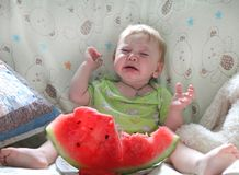 Плача младенец сидит на кровати в светлой комнате Стоковое Изображение