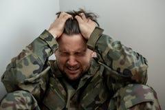 Плача профессиональный солдат с депрессией и травмой после войны стоковое фото rf