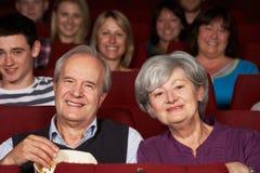 Пленка старших пар наблюдая в кино стоковые изображения