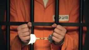 Пленник показывая руки в наручниках, опасное уголовное положение за решеткой сток-видео