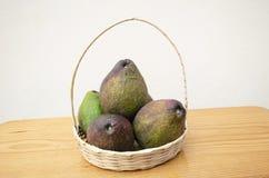 Плетеная корзина заполненная с авокадоами стоковая фотография