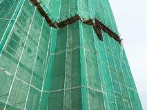 Плетение безопасности установлено на высокий подъем строя внешние леса во время конструкции стоковые фото