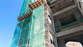 Плетение безопасности установлено на высокий подъем строя внешние леса во время конструкции стоковая фотография