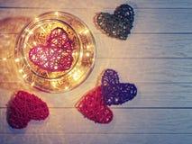 Плетеное сердце в большом стеклянном опарнике с объектами светящей гирлянды внутренними и декоративными Стоковые Фото