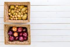 2 плетеных корзины с свежими картошками и луками Стоковое Изображение