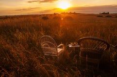 2 плетеных стуль и поднос с стеклами вина между полями на заходе солнца Стоковое фото RF