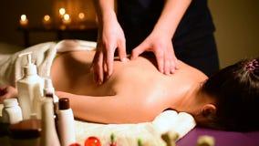 Плечи и задняя часть ` s женщины массажа курорта конца-вверх Мужские руки массажируют к женщине в темной комнате с свечами в видеоматериал