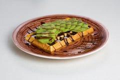Плита бельгийских waffles с кивиом, сливк и шоколадом Стоковое Изображение