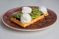 Плита бельгийских waffles с кивиом, сливк и шоколадом Стоковые Изображения