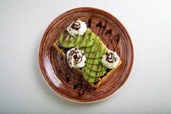 Плита бельгийских waffles с кивиом, сливк и шоколадом Стоковые Фото