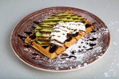 Плита бельгийских waffles с кивиом, сливк и шоколадом Стоковое Фото