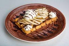 Плита бельгийских waffles с сливк, бананами и шоколадом Стоковое Изображение
