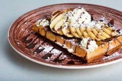 Плита бельгийских waffles с сливк, бананами и шоколадом Стоковые Изображения
