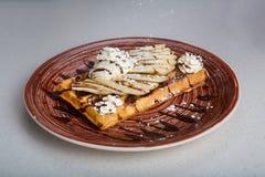 Плита бельгийских waffles с сливк, бананами и шоколадом Стоковые Фото
