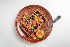 Плита бельгийских waffles с сливк, candied и шоколадом Стоковые Изображения RF