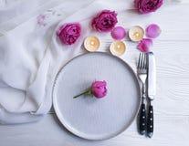Плита, вилка, нож, свеча, розовое датировка торжества меню датировка приглашения цветка на деревянной предпосылке стоковое изображение