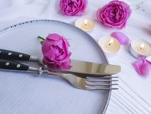Плита, вилка, нож, свеча, розовое датировка торжества меню датировка цветка на деревянной предпосылке стоковая фотография