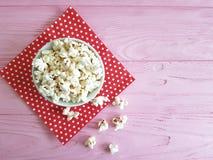 Плита естественная, красная салфетка попкорна в предпосылке пинка точки польки деревянной с космосом для текста Стоковое Изображение