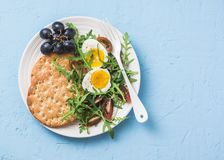 Плита завтрака - вся шутиха пшеницы, arugula, томаты вишни, салат вареного яйца на голубой предпосылке Стоковое Изображение