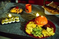 Плита закуски партии хеллоуина с высекаенной тыквой, nachos, гуакамоле и сальса окунают Стоковые Фото