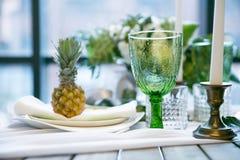 Плита и стекло на таблице украшенной с цветом ананаса, свечи и цветков, зеленых и белых Стоковое Фото