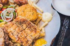 Плита мяса еды большого комплекта греческая с картошками и соусом стоковое изображение