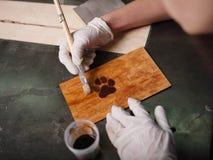 Плита на которой лапка латает scorches и надписи Стоковые Изображения