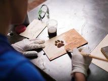 Плита на которой лапка латает scorches и надписи Стоковая Фотография