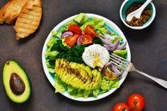 Плита овоща с салатом, луком, томатами, авокадоом и яйцом стоковое изображение