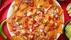 Плита очень вкусных nachos tortilla с расплавленным соусом сыра, зажаренным цыпленком сток-видео