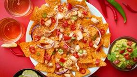 Плита очень вкусных nachos tortilla с расплавленным соусом сыра, зажаренным цыпленком видеоматериал