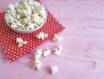 Плита попкорна, красная салфетка в предпосылке пинка точки польки деревянной с космосом для текста Стоковое Фото