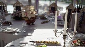 Плита, салфетка ткани, нож и вилка на белой ткани на таблице в ресторане акции видеоматериалы