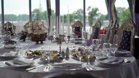 Плита, салфетка ткани, нож и вилка на белой ткани на таблице в ресторане сток-видео