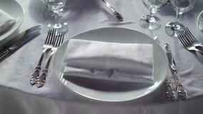 Плита, салфетка ткани, нож и вилка на белой ткани на таблице в ресторане видеоматериал