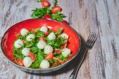Плита свежего салата с arugula, томатами вишни, сыром моццареллы на белом, затрапезный, деревянный стол Вертикальный взгляд экзем стоковое изображение