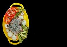 Плита стейка и овощей на желтой плите на черной предпосылке с космосом для текста стоковое фото rf