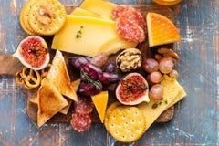 Плита сыра служила с виноградинами, вареньем, смоквами, медом, шутихами и гайками на серой предпосылке скопируйте космос Взгляд с стоковое изображение
