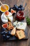 Плита сыра с виноградинами, смоквами, шутихами, медом, студнем сливы, тимианом и гайками стоковое фото rf