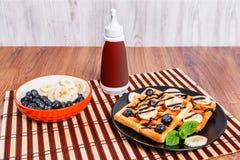 Плита с бельгийскими waffles и бутылкой с соусом шоколада Стоковое Изображение